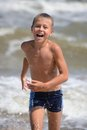 Boy running on the beach brave Stock Images
