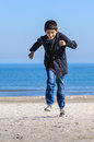 Boy running on beach in fall clothes Royalty Free Stock Image