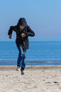 Boy running on beach in fall clothes with hood Royalty Free Stock Photos