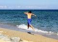 Boy running on the sea beach summer holidays Stock Photos