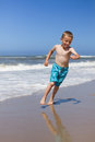 Boy running and smiling at beach a young caucasian is having a great time in circles fleeing from the ocean waves sunlit sand in Stock Photography
