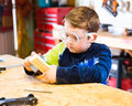 Boy sanding wooden block in workshop as he builds car for pinewood derby Royalty Free Stock Photography