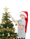 Boy with santa hat decorates the Christmas tree Stock Photos