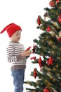 Boy in santa hat decorating christmas tree isolated on white Stock Photo