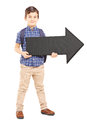 Boy with school bag holding a big black arrow pointing right full length portrait of isolated on white background Royalty Free Stock Images