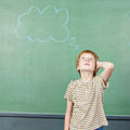 Boy in school thinking with thought elementary bubble drawn on chalkboard Royalty Free Stock Image
