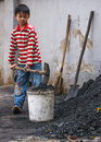 Boy scoops coal in bucket. Royalty Free Stock Photo