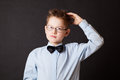 Boy scratching his head thinking on black background Royalty Free Stock Photos