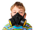 Boy screw up ones eyes in black respirator Royalty Free Stock Photo