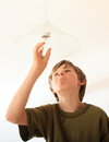 Boy screwing bulb concentrated on a lamp Royalty Free Stock Image