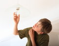 Boy screwing bulb concentrated on a lamp Royalty Free Stock Photos