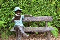 Boy sculpture in the garden reading book Royalty Free Stock Photo