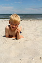 The boy on the sea beach lies Stock Photography