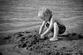 Boy at the seaside little is playing sand castle Stock Images