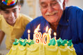 Boy and Senior Man Blowing Candles On Cake Birthday Party Royalty Free Stock Photo