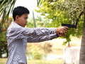 Boy shooting air soft ball bullet gun asian male teenager young thai wearing light blue shirt black model of a replica real pistol Royalty Free Stock Photography