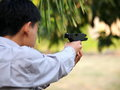 Boy shooting air soft ball bullet gun backside of an asian male teenager young thai wearing light blue shirt black model of a Royalty Free Stock Images