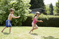 Boy shooting girl with water pistol in backyard full length side view of a the Stock Photography