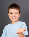 Boy show lost tooth in the palm on gray Royalty Free Stock Image