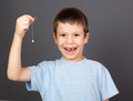 Boy show lost tooth on a thread gray Stock Photography