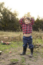 Boy showing belly button smiling standing in a watermelon patch raising his hands and his Stock Photography