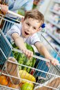 Boy sits in the cart with watermelon little and other products bought by parents Stock Images