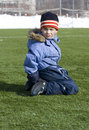 The boy sits on the football field. Royalty Free Stock Photo