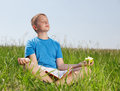 The boy sits on a grass and eats a green apple Stock Images
