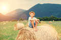 Boy sits on the haystack top Royalty Free Stock Photo
