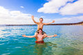 Boy sits on his brother s shoulders in the ocean clear blue water of an bay Stock Photos