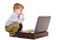 Boy sits at a notebook little thoughtfully Royalty Free Stock Photos