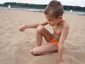 Boy sits on sand plays with at the beach Stock Photo