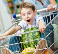 Boy sits in the shopping trolley with watermelon and other products bought by parents Stock Photos