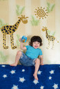 A boy sits on the sofa in the room and drink with wallpaper with giraffes of cup for babies Royalty Free Stock Photo