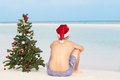 Boy sitting on beach with christmas tree and hat relaxing Stock Images