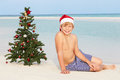 Boy sitting on beach with christmas tree and hat smiling Royalty Free Stock Photo
