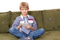 Boy sitting on bed and play with tablet pc Stock Images