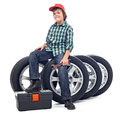 Boy sitting on car tires holding spanner isolated Stock Image