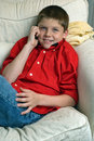 Boy sitting in chair talking on cell phone Royalty Free Stock Photo