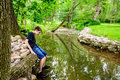 Boy sitting at edge of stream getting shoes wet an year old the a and his Stock Photography