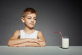 Boy sitting with glass of milk over grey background Royalty Free Stock Photos