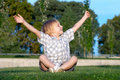 Boy sitting on a grass with the lifted hands Royalty Free Stock Photo