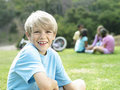 Boy sitting on grass in park smiling portrait focus on foreground Royalty Free Stock Photos