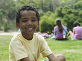 Boy sitting on grass in park smiling portrait focus on foreground Royalty Free Stock Image