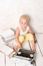 Boy sitting near retro typewriter and books on white painted floor Stock Photo