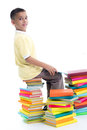 Boy sitting on a pile of books and learn holding one book in his hands Stock Photos