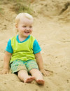 Boy sitting at sand beach Stock Images