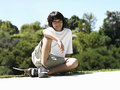 Boy sitting on skateboard in park smiling portrait Stock Photo
