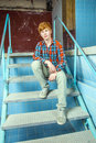 Boy sitting on the stairs of an old waterless pool Royalty Free Stock Image