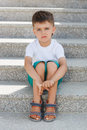 The boy sitting on the stairs in the underpass little brunette with short hair wearing a white t shirt and green shorts with a sad Royalty Free Stock Image
